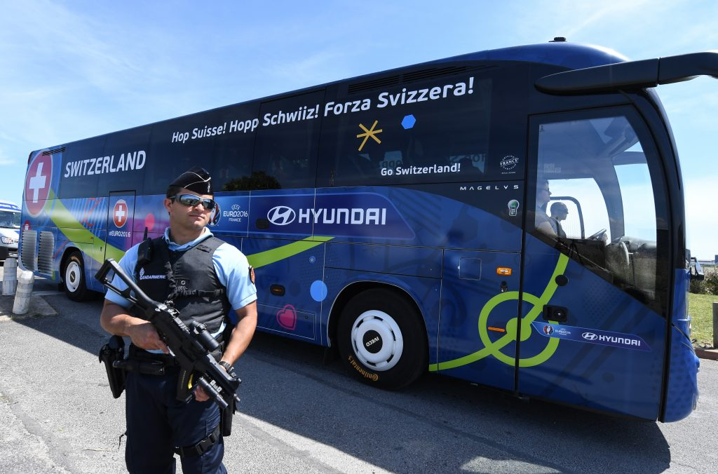 A policeman stands guard as Switzerland's national football team leaves Montpellier's airport by bus, on June 6, 2016, four days ahead of the start of the Euro 2016 European football championships. / AFP PHOTO / PASCAL GUYOT